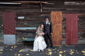 Bride sitting on the bench holding hads with a groom — Stock fotografie