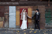 Bride and a groom standing near the building — Stock fotografie