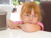 Little girl sits at a table — Stock Photo