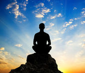 Silhouette of the meditating person — Stock Photo