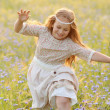 Baby girl in a long dress running through a field of rye — Stock Photo