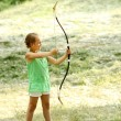 Baby girl shoots a bow — Stock Photo