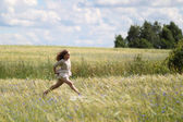 Baby girl in a long dress in the middle of the field laughing — Stock Photo