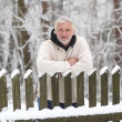 An attractive middle-aged gray man stands near the fence — Stock Photo