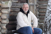 The attractive gray-haired elderly man sits beside log home — Stock Photo