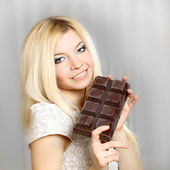Nice natural cute blonde girl eating a large bar of chocolate — Stock Photo