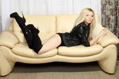 Charming slim blonde girl in a leather jacket with boots lying on a white sofa — Stock Photo