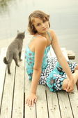 Teen girl sitting on a wooden platform near the water with a gray cat — Stock Photo
