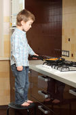 Little boy cooking near the gas stove — Stock Photo