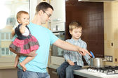 Happy father with children in the kitchen — Stockfoto