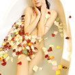 Woman in a bath with rose petals - Stock Photo