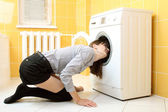 Ordinary simple beautiful girl put her head into a washing machine — Stok fotoğraf