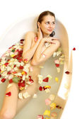 Woman in a bath with rose petals — Stock Photo