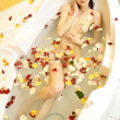 Nude attractive girl lying in a bath with rose petals — Stock Photo