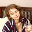 A woman in a bathrobe suffering from headache - Stock Photo