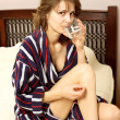 Woman in a bathrobe suffering from a headache - Stock Photo
