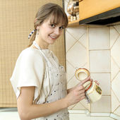 Nice normal girl in a light dress takes a spoonful of sugar — Stock Photo