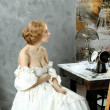 Woman in vintage dress sitting near retro sewing machine — Stock Photo