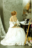 Woman in vintage dress sitting near retro sewing machine — Stok fotoğraf