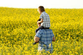 Father with son in a yellow field — Stok fotoğraf