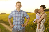 Mother and father with their little daughter in a field — Stockfoto