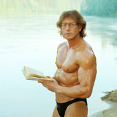 Naked bodybuilder beautiful man reading on the beach — Stock Photo