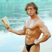 Naked bodybuilder beautiful man reading on the beach — Stock Photo