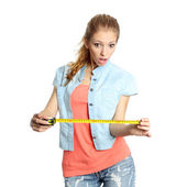 Concerned girl looks down at tape measure — Stock Photo