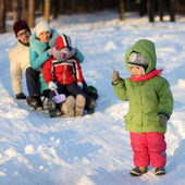 Attractive family having fun in a winter park — Stock Photo