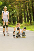 Mother and daughter learn to roller skate — Стоковое фото