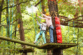 Mother and daughter in climbing equipment to overcome obstacles between high trees — Stock Photo
