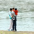 Mom, dad and baby in his arms looking at the river — Foto de Stock
