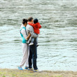 Mom, dad and baby in his arms looking at the river — Stock Photo #44731737