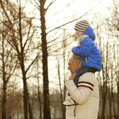 Grandfather carries grandson on his shoulders — Stock Photo