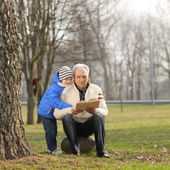 Grandfather and grandson reading a book outdoors — Stok fotoğraf