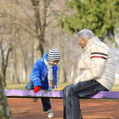 Grandfather and grandson playing chess on a bench outdoors — Stock Photo