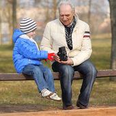 Grandfather shows grandson vintage camera — Stock Photo