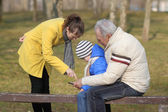 Grandfather and grandson are looking tablet on bench outdoors — Stock Photo