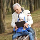 Dědeček a vnuk hledají tabletu na lavičce venku — Stock fotografie