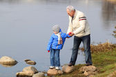 Grandfather and grandson on stones near the water — Stock Photo