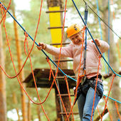 Climber woman engaged in training between trees — Stock Photo