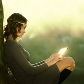 Hipster girl using tablet sitting near a tree at sunset — Photo