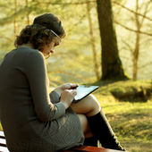 Hipster girl using tablet sitting near a tree at sunset — Stock Photo