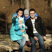 Beautiful young family of four on nature at the sunset — ストック写真