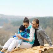 Schöne junge Familie liegend auf einer Decke und Blick auf tablet — Stockfoto