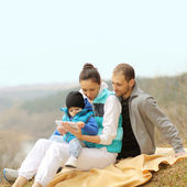Beautiful young family lying on a blanket and looking at tablet — Stock Photo
