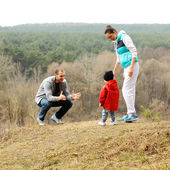 Beautiful young sporty family stands back on the mountain — 图库照片