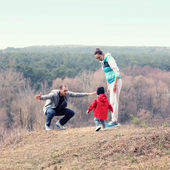 Beautiful young sporty family stands back on the mountain — Zdjęcie stockowe