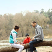 Young family sitting on a tree near the river — 图库照片