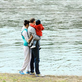 Mom, dad and baby in his arms looking at the river — 图库照片